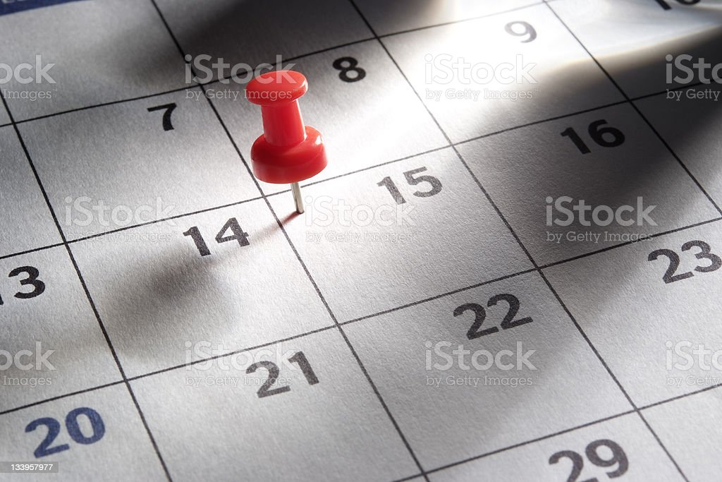 Red thumbtack in calendar with light rays royalty-free stock photo
