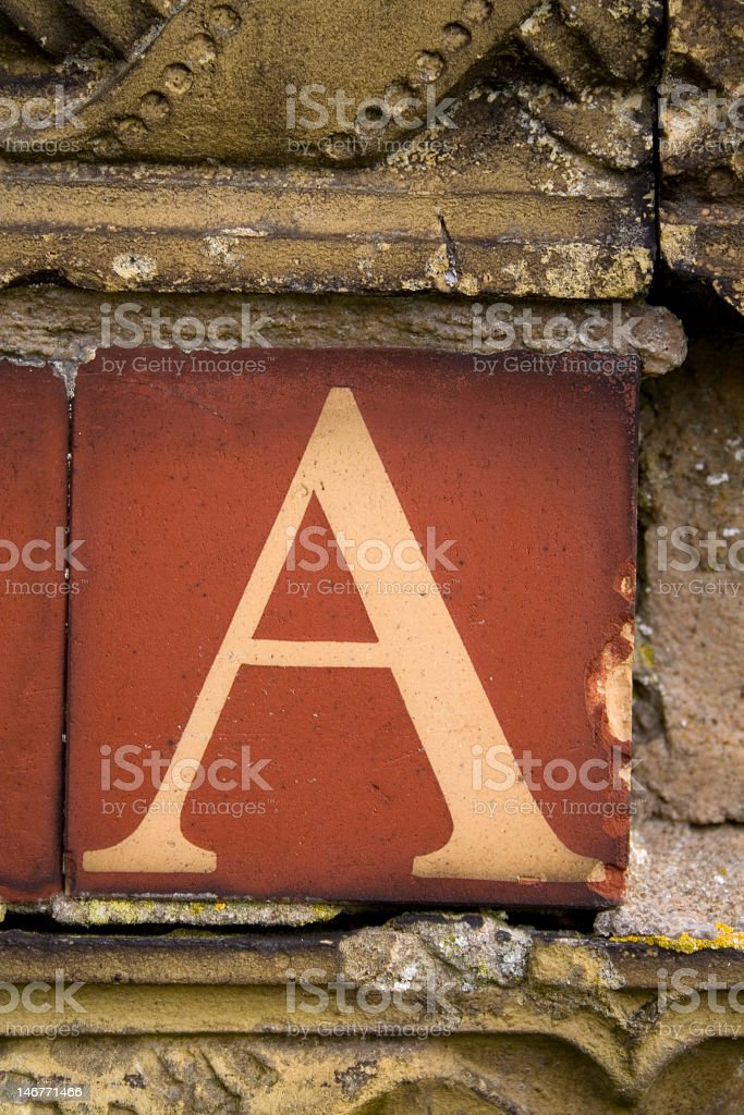 A red tile with the letter A on an old wall stock photo
