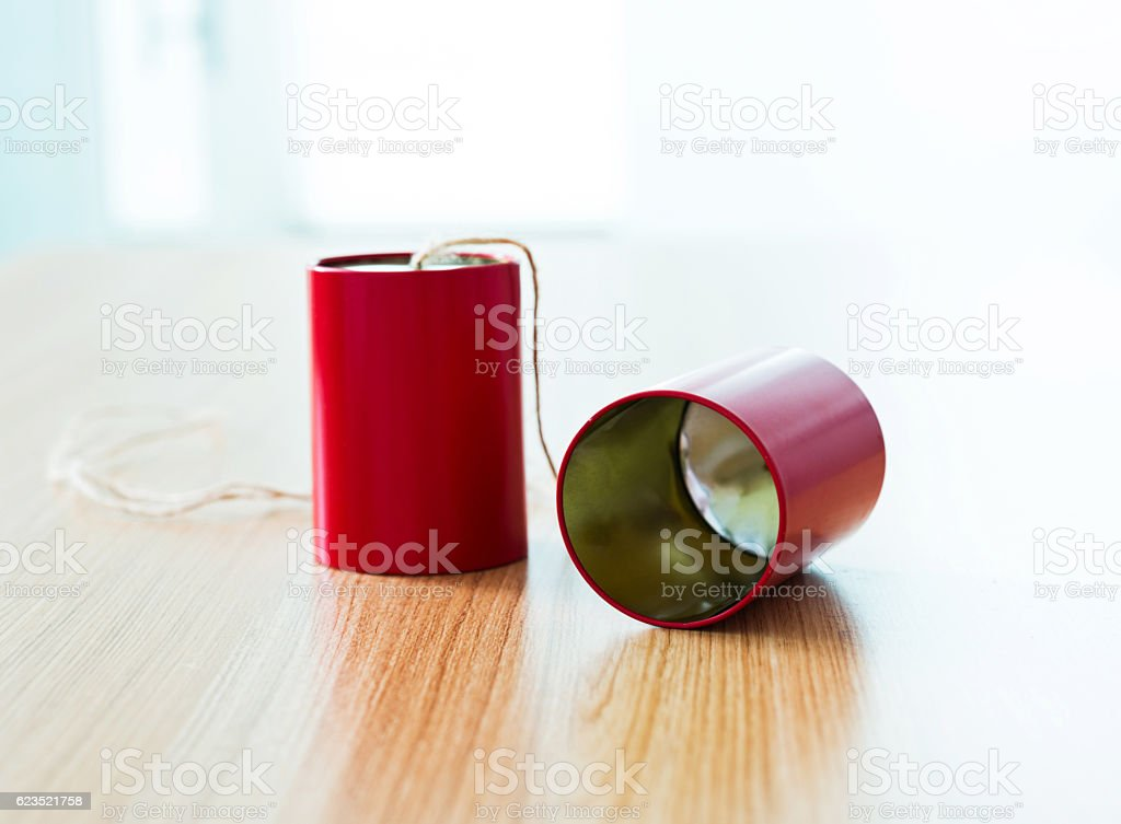 Red tin can phone on desk stock photo