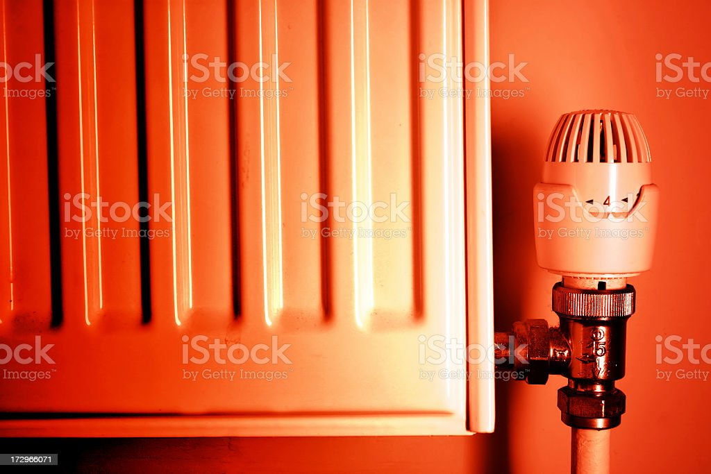 Red tinted photo of a thermostat and radiator stock photo