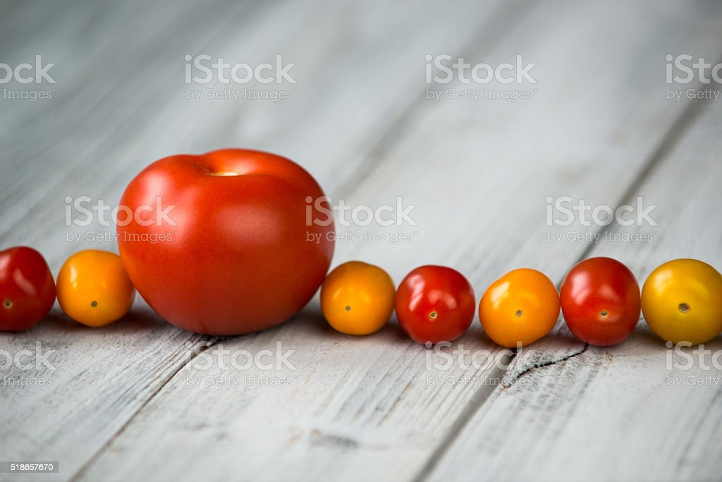 Red tomato and cherry tomatoes on a wooden background stock photo