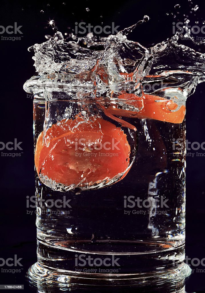 Red tomato falling down in glass with water royalty-free stock photo