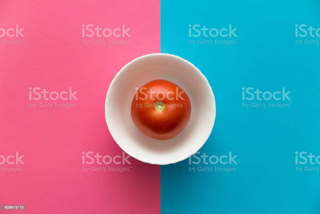 Red tomato in bowl on serenity blue rose quartz background stock photo