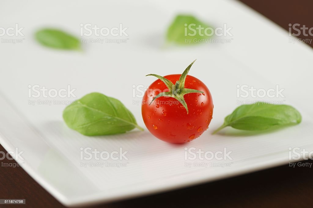 Red tomato with basil leaves on white plate stock photo