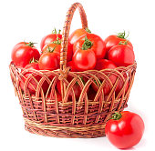 red tomatoes in a wicker basket isolated on white background