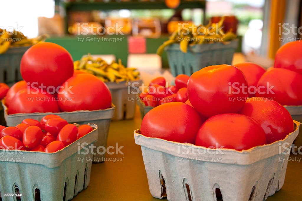 Red Tomatoes in small containers  at a road side stand stock photo