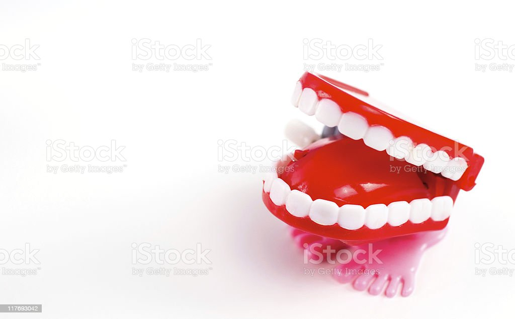 Red toy chattering teeth with pink feet isolated on white stock photo