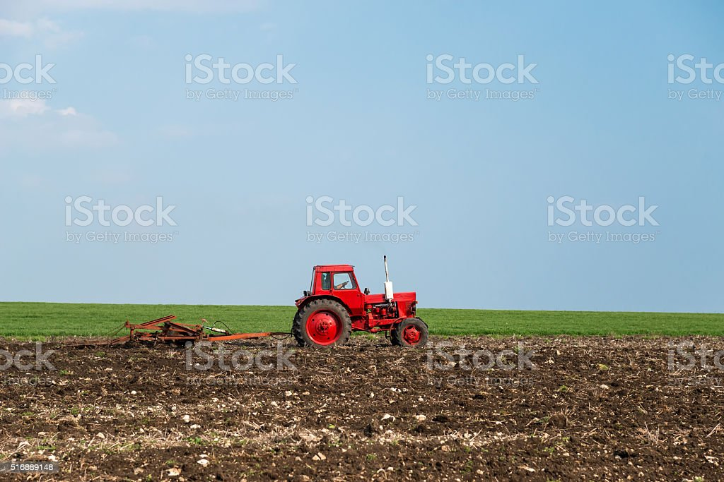 red tractor in the agricultural field stock photo