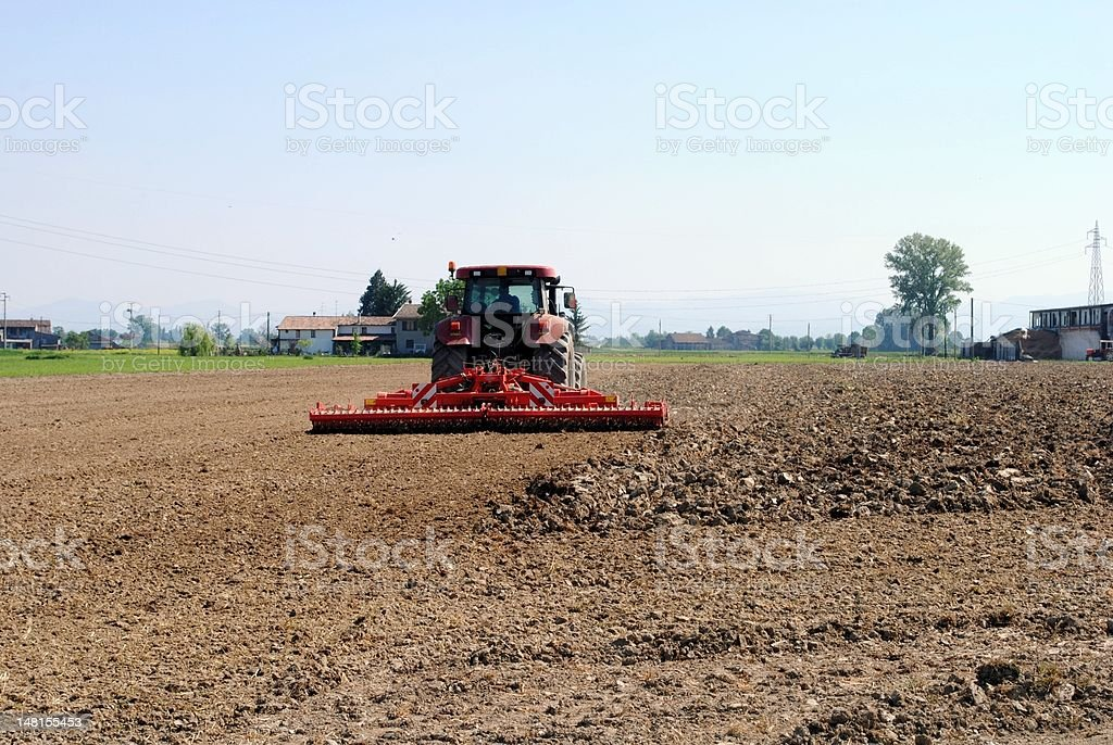 red tractor prepares soil stock photo