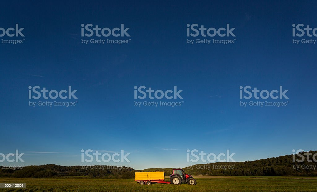 Red tractor with yellow trailer stock photo