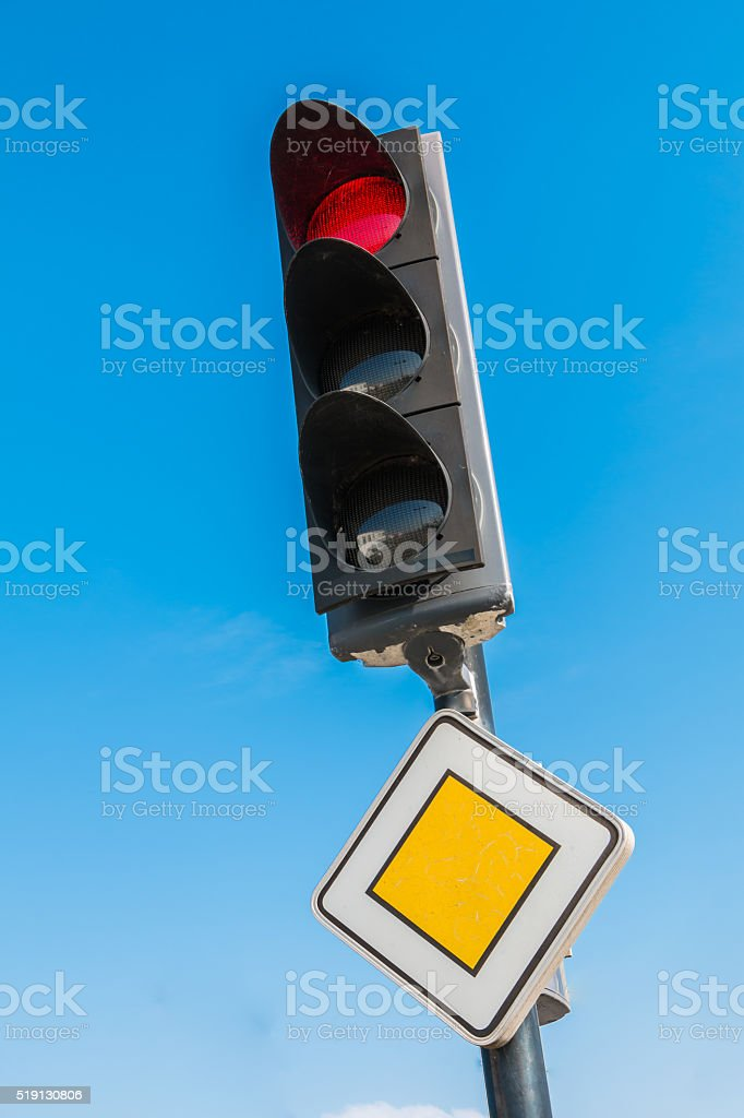 red traffic light with priority road sign stock photo