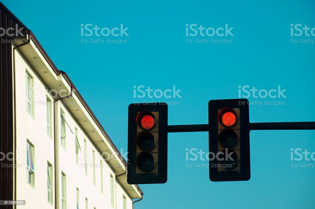 Red traffic lights, apartment buildings, clear blue sky. stock photo