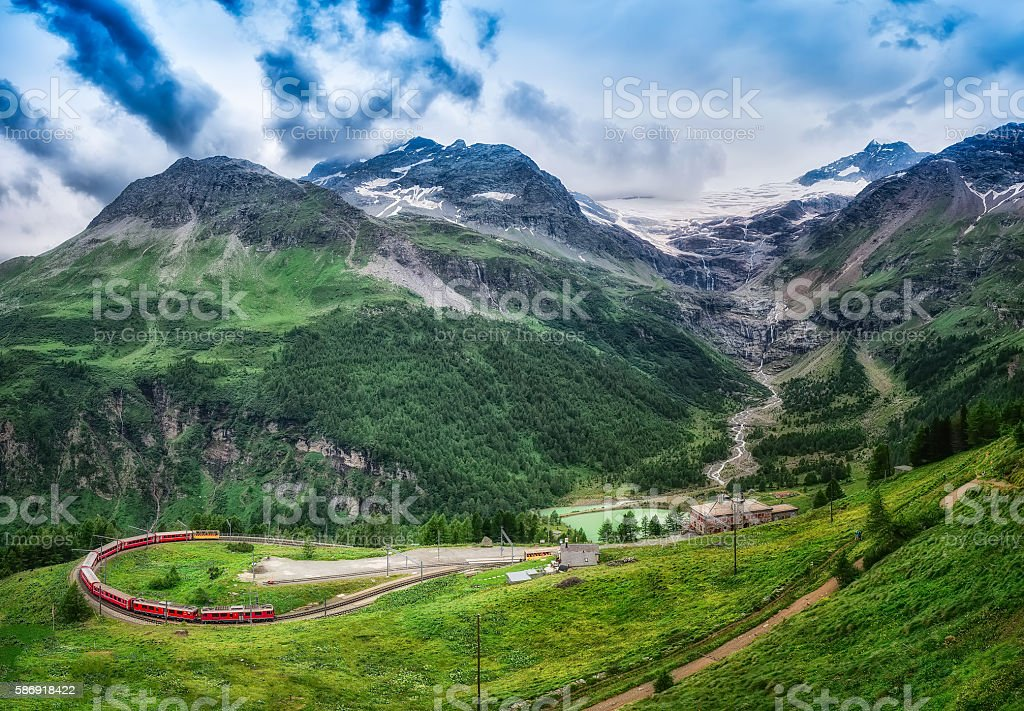 Red train Bernina Express to the passage in the mountains. stock photo