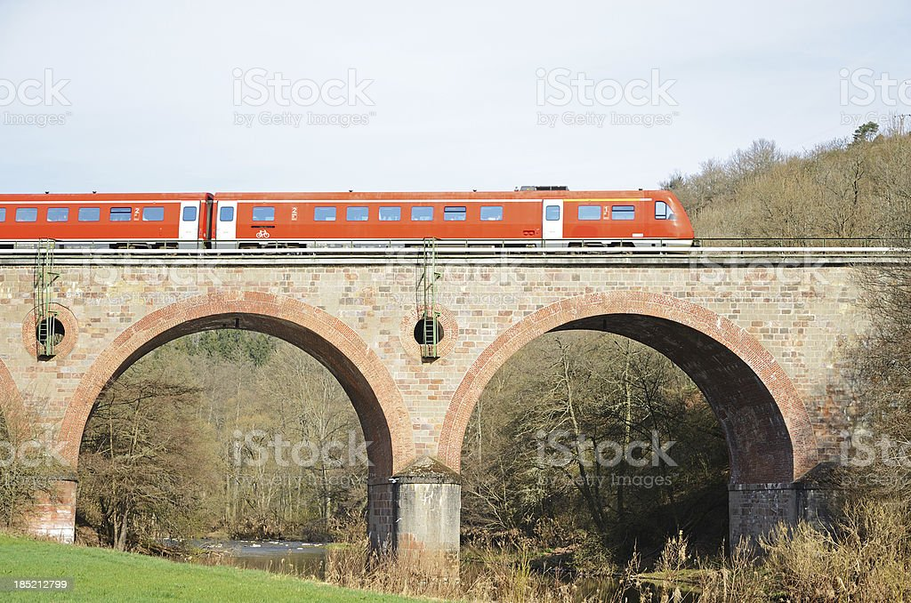 Red train on arch bridge over river royalty-free stock photo