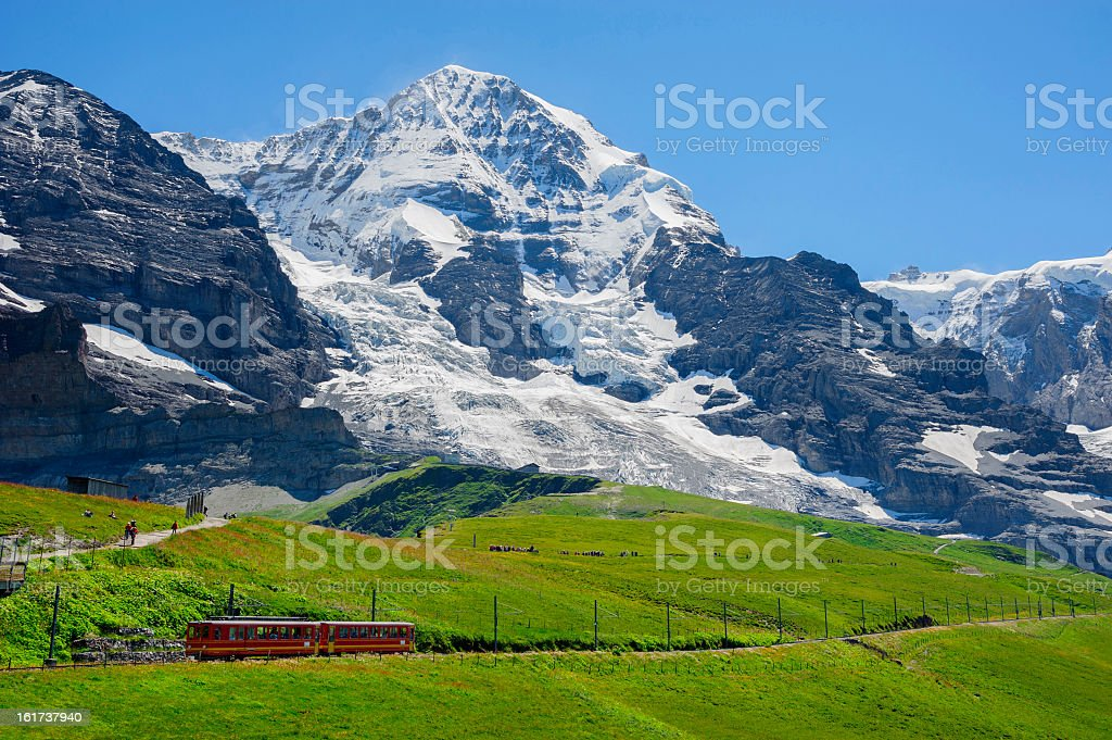 Red train passes by white mountains of Jungfrau, Switzerland stock photo