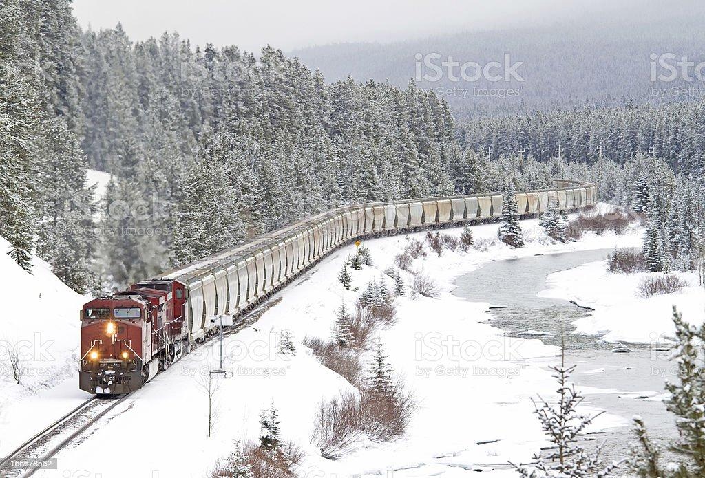 Red Train Speeding Through Rocky Mountains royalty-free stock photo