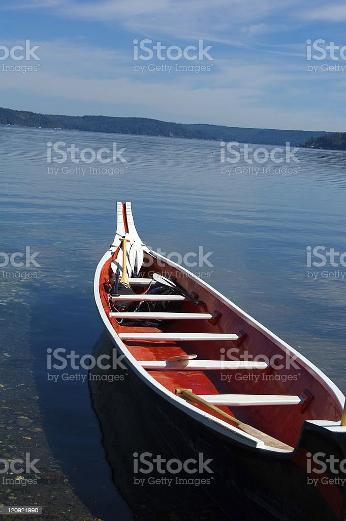 Red tribal canoe on calm blue waters- Washington State royalty-free stock photo
