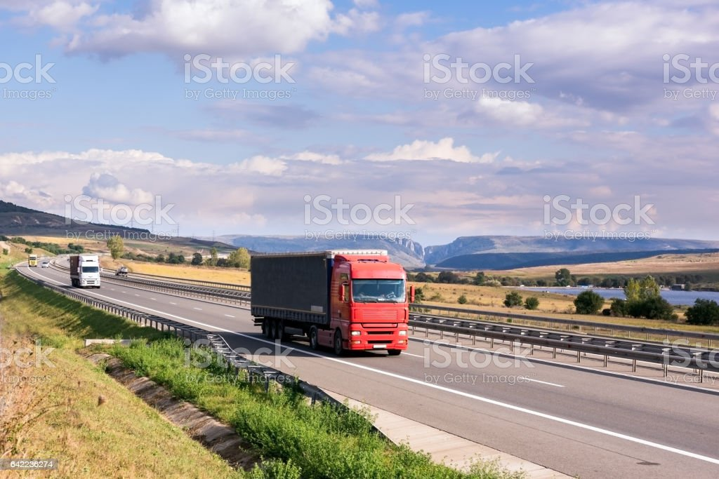 Red truck carrying cargo on the highway stock photo