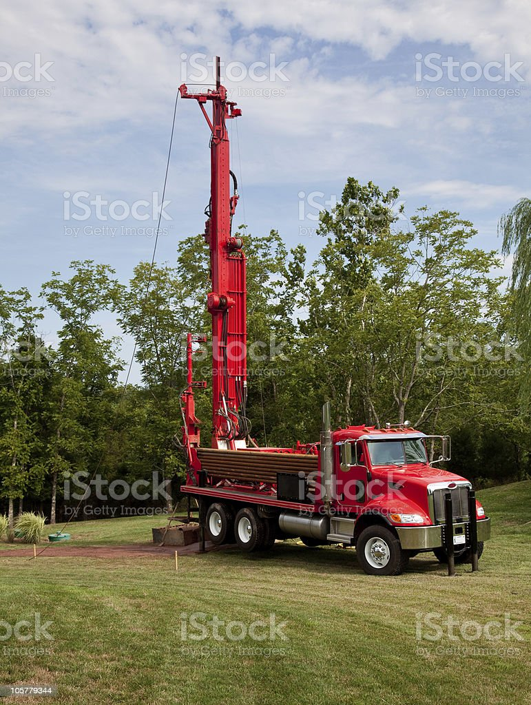 Red truck drilling for geothermal power in yard stock photo