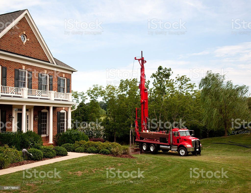 Red truck drilling into the yard stock photo
