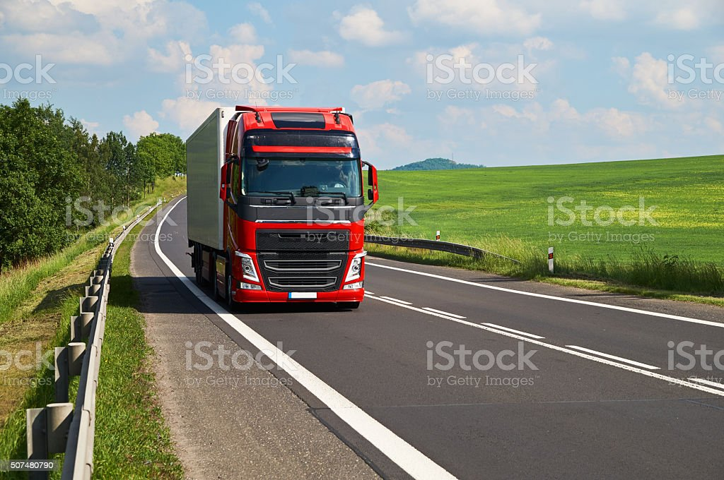 Red truck driving on asphalt road in a rural landscape stock photo