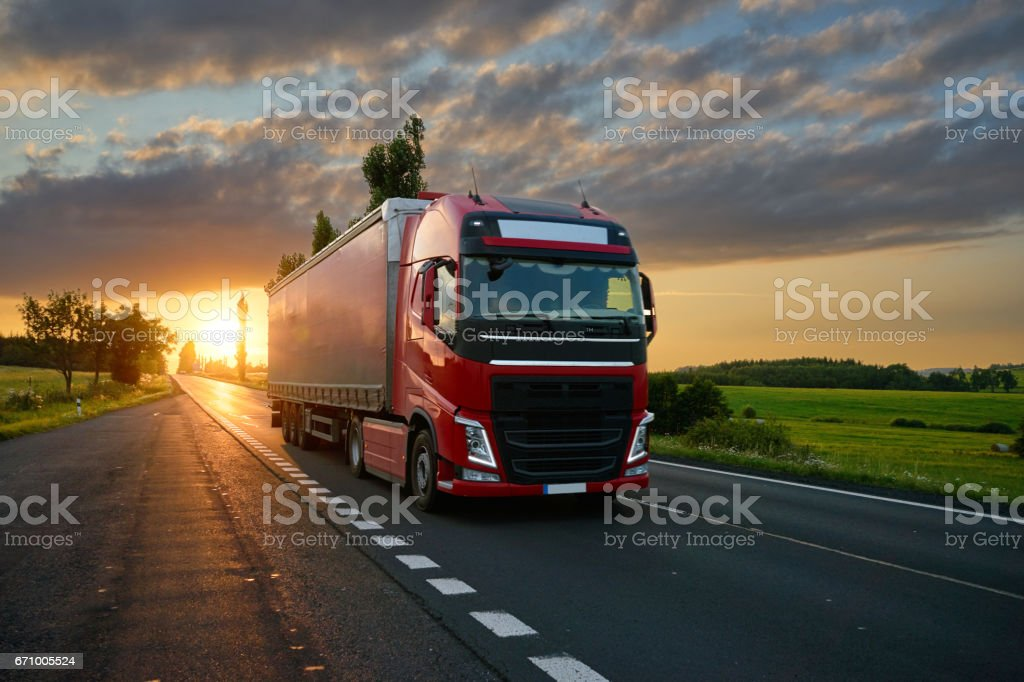 Red truck driving on the road at sunset stock photo