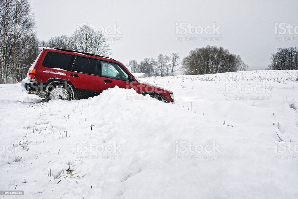 Red truck stuck in a ditch in the wintertime stock photo