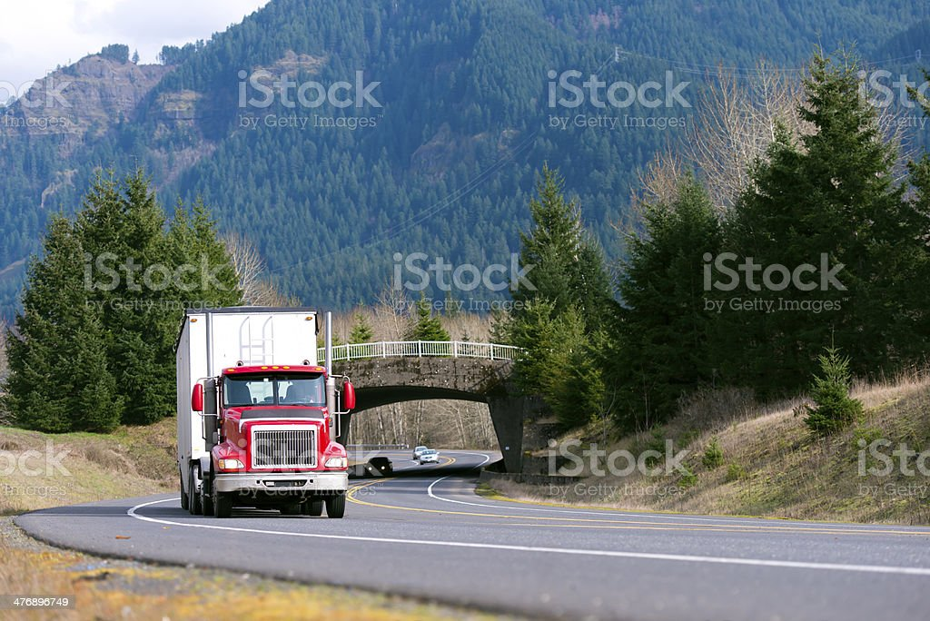 Red truck with white trailer in front of bridge stock photo