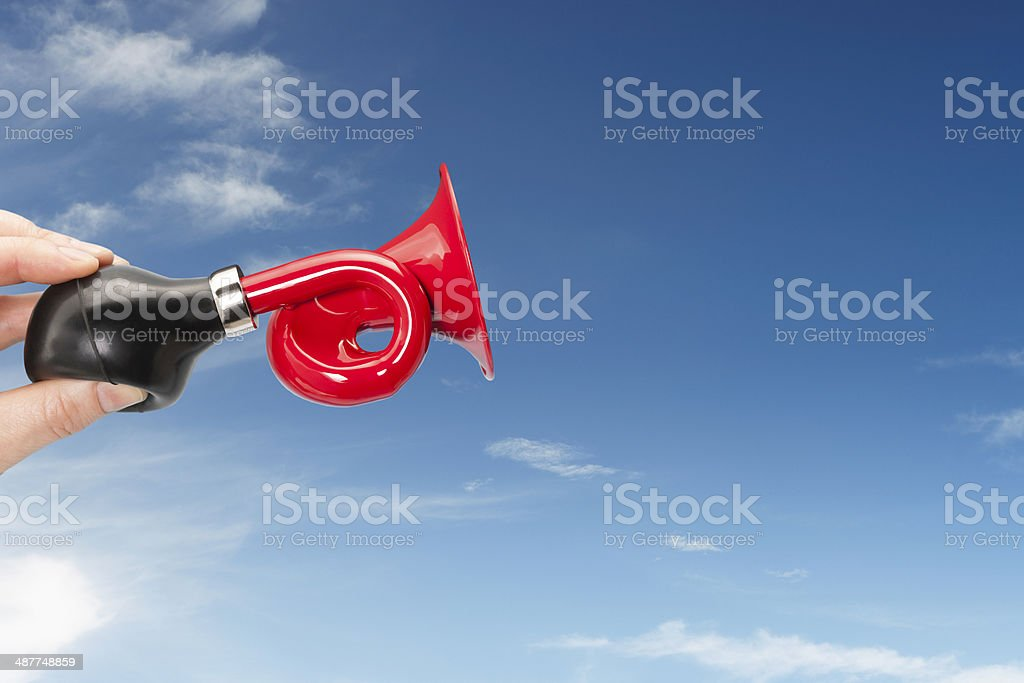 Red trumpet announcement against blue sky stock photo