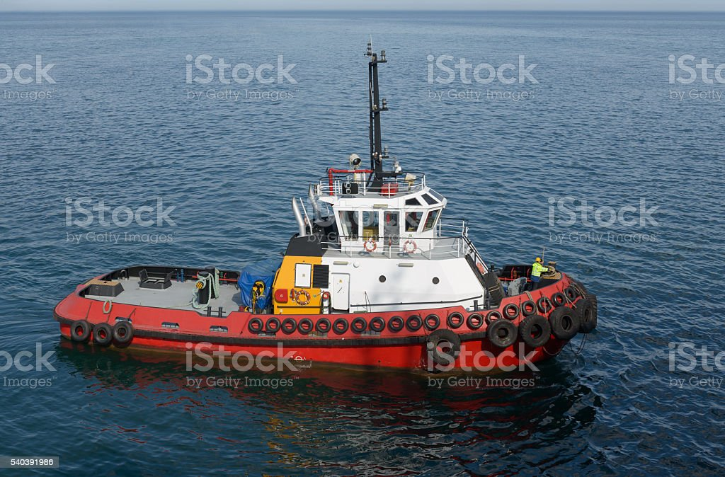 Red tug boat on  water stock photo
