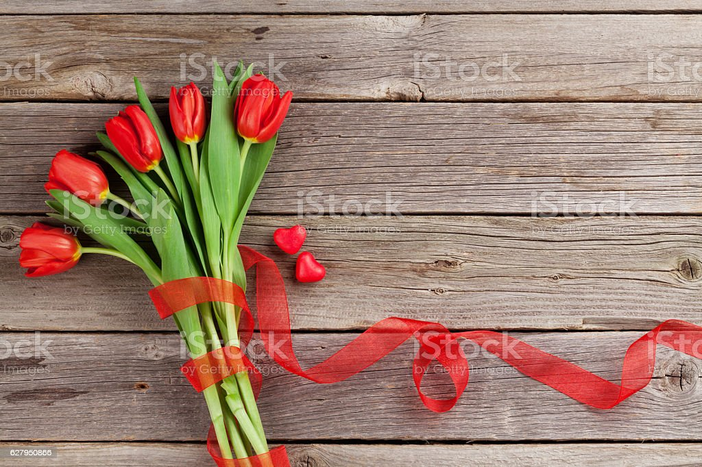 Red tulips and candy hearts stock photo