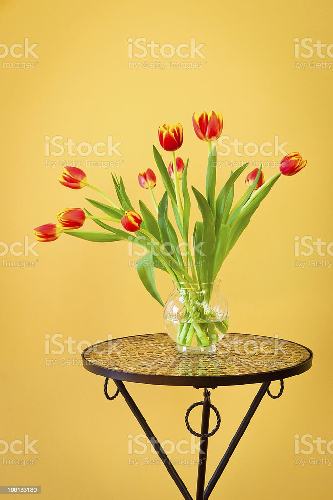 Red tulips in a vase on mosaic table. royalty-free stock photo