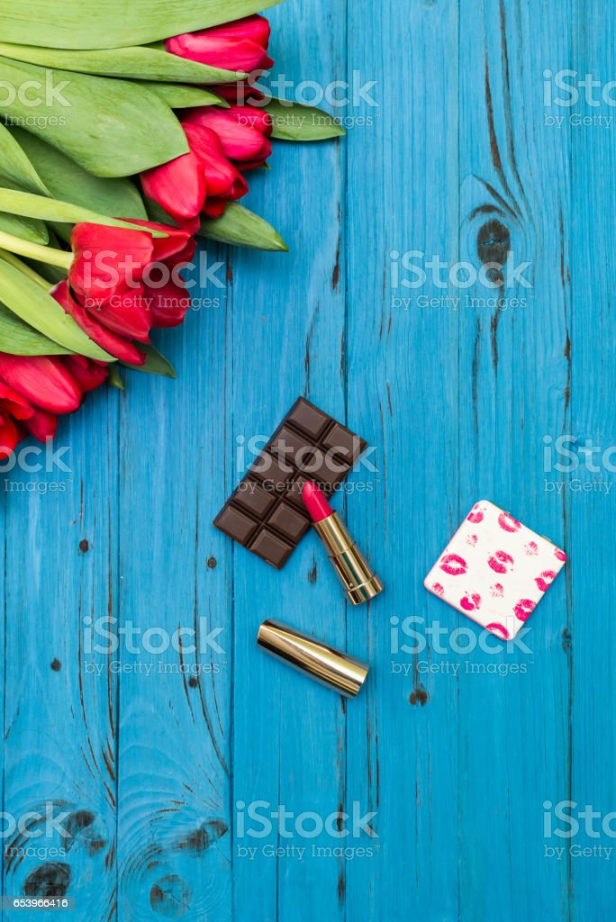 red tulips on a blue wooden board stock photo