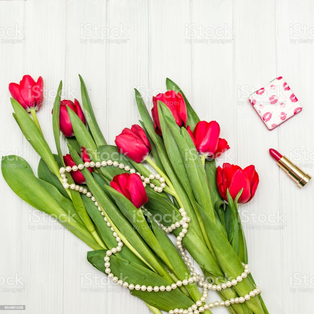 red tulips on a white wooden board stock photo