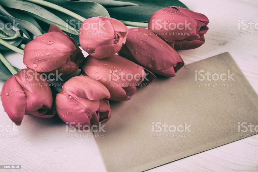 Red tulips with paper sheet. Vintage style retro still life stock photo