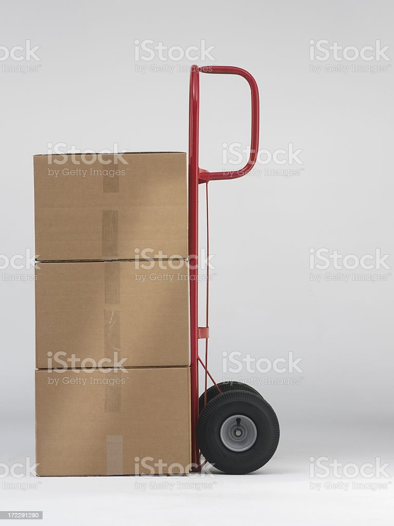 red two wheel dolly with three corrugated brown boxes stock photo