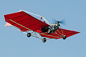 red ultralight aircraft Snedden M7 flying in clear lue sky