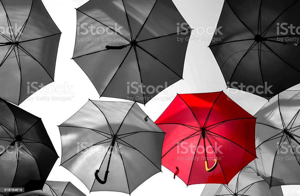 red umbrella standing out from the crowd stock photo