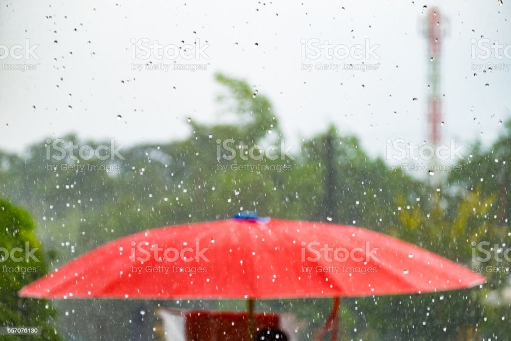 Red umbrella with storm fall rain stock photo