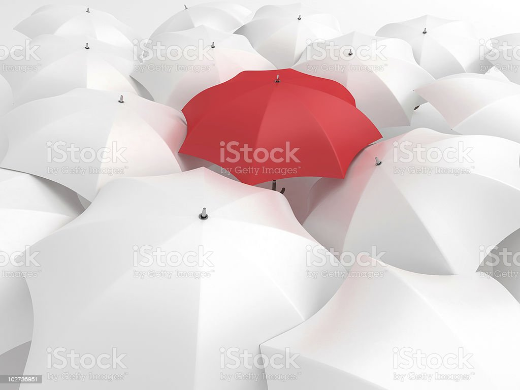 Red umbrella with white umbrellas stock photo