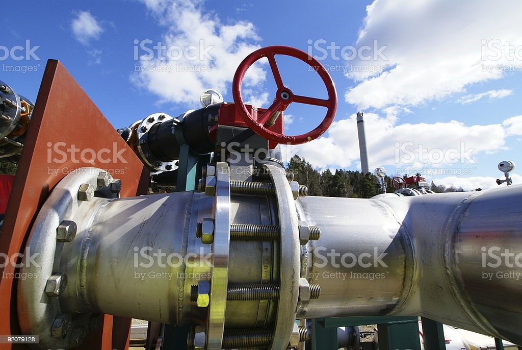 red valve and piping against blue sky royalty-free stock photo