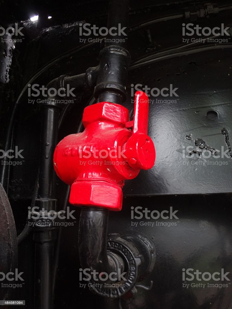Red valve on a black pipe stock photo