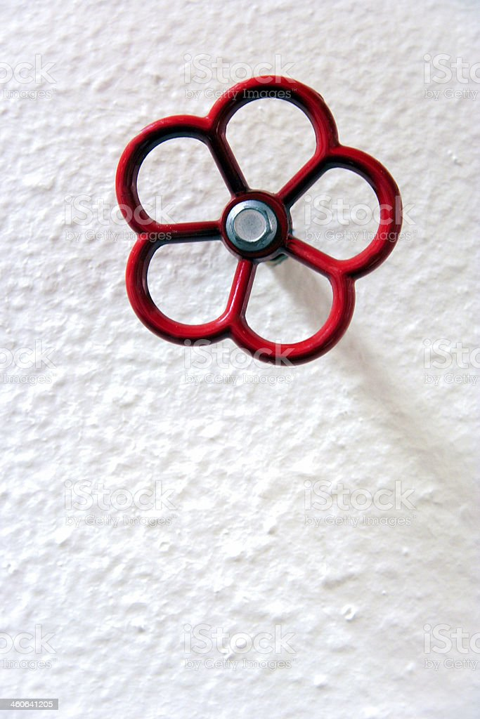 Red valve on white wall stock photo