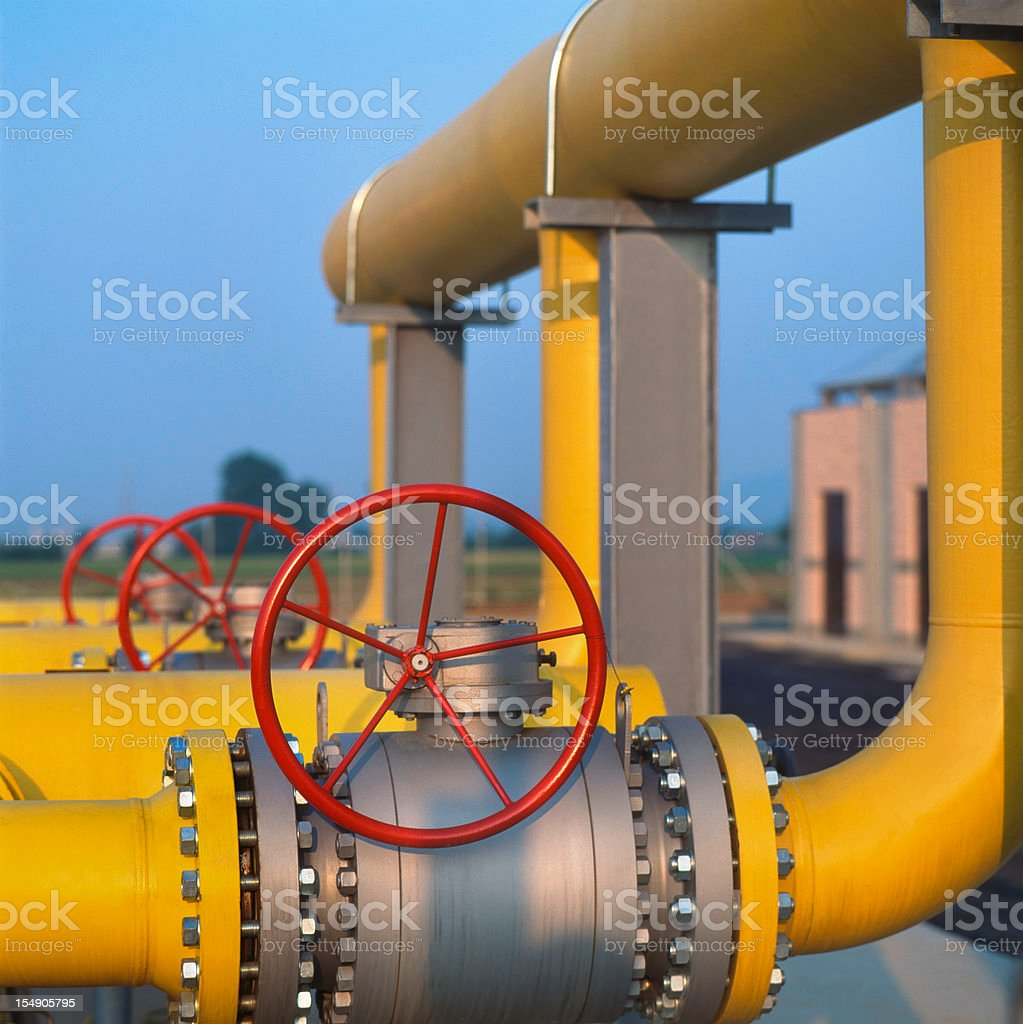 Red valve on yellow pipes in natural gas distribution station stock photo