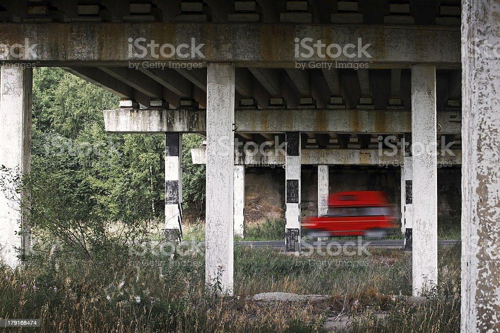 Red van car goes fast under old bridge royalty-free stock photo