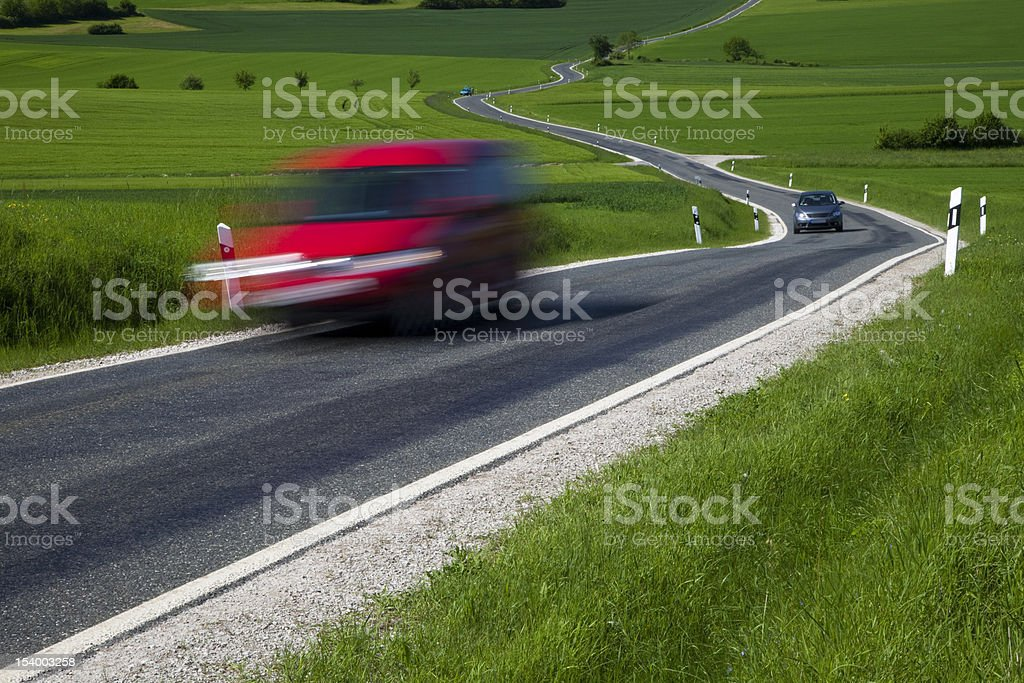 Red Vehicle Driving Fast on Winding Road royalty-free stock photo