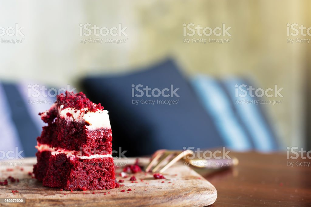 Red velvet cake was chipped on wooden plate with fork stock photo