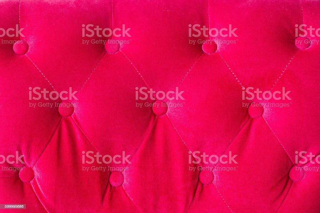 Red velvet couch background texture with sunken buttons stock photo
