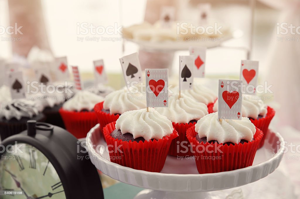 Red velvet cupcakes with playing cards toppers, Alice in wonderland stock photo