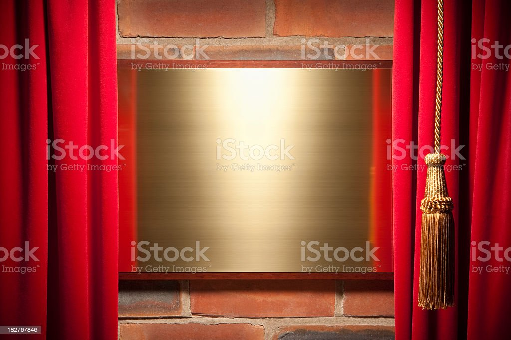 Red velvet curtain reveals blank brass plaque royalty-free stock photo